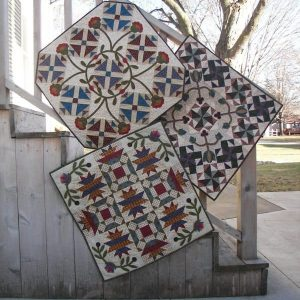 scrappy pieced blocks with floral applique wall hangings