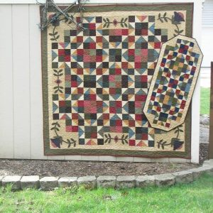 Scrappy stars and appliqued floral motif lap quilt and runner